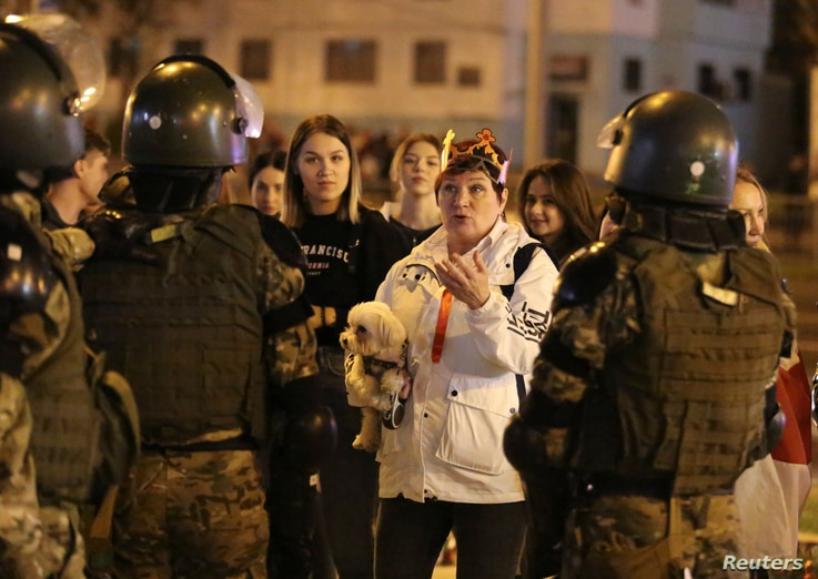 A woman holding a dog talks to Belarusian law enforcement officers during an opposition protest.