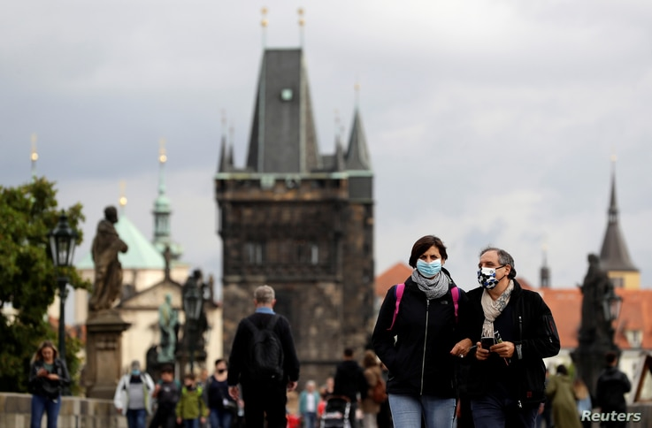 People wearing face masks walk across the medieval Charles Bridge as the spread of the coronavirus disease (COVID-19) continues…