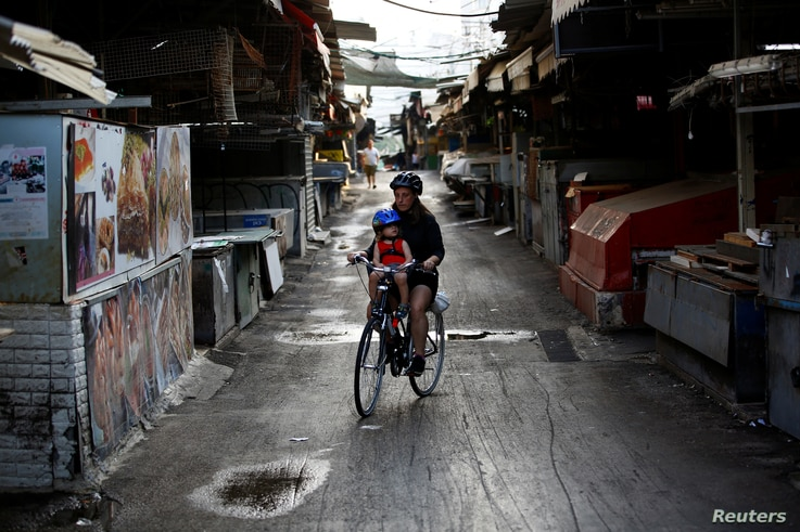 A woman rides a bicycle with her child in a closed market after Israel imposed a second nationwide coronavirus disease (COVID…