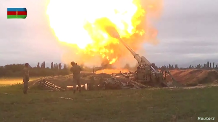 A still image from a video released by the Azerbaijan's Defense Ministry shows members of Azeri armed forces firing artillery.