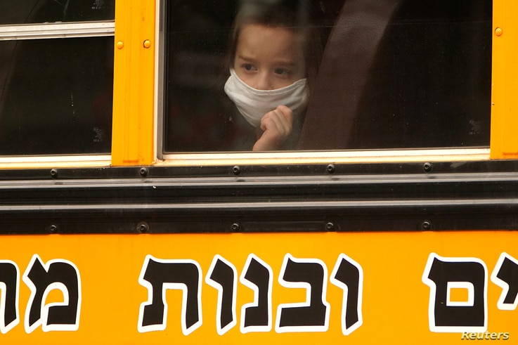 A child wears a mask on a school bus in the Borough Park section of Brooklyn, New York City, New York, U.S., September 29, 2020…