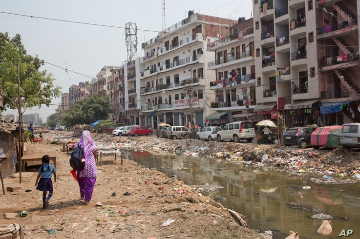 An Indian woman walks with a child along an open drain filled with plastic and stagnant water which act as a breeding ground…