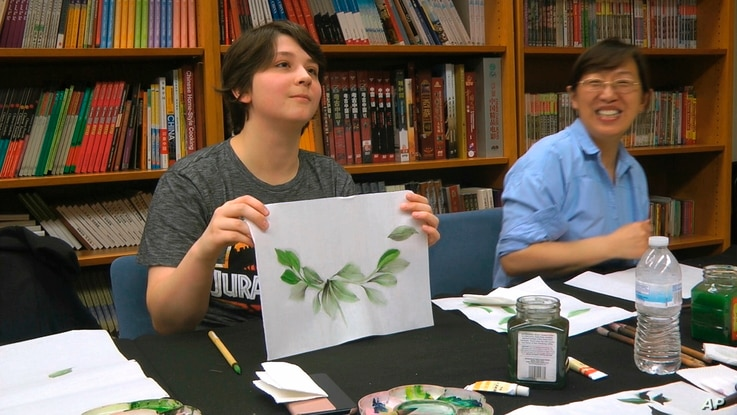 Undergraduate student Moe Lewis, left, shows her watercolor painting of peony leaves at a traditional Chinese painting class at…