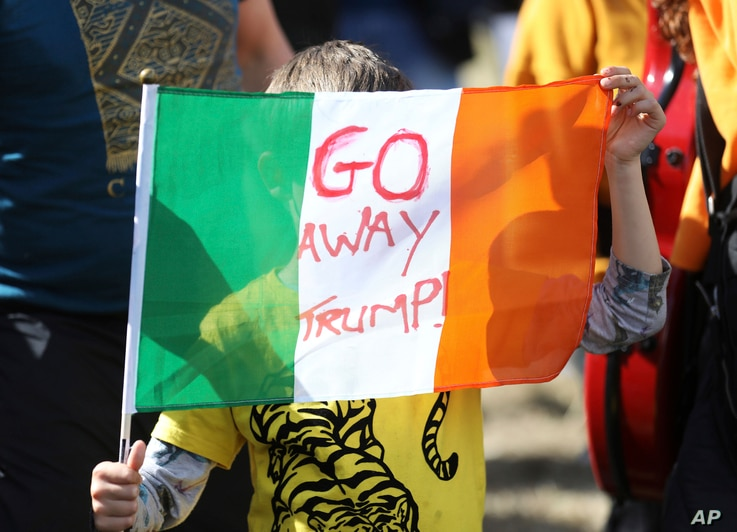 A demonstrator protests before the arrival of U.S President Trump at Shannon Airport in the west of Ireland, Wednesday, June 5,…