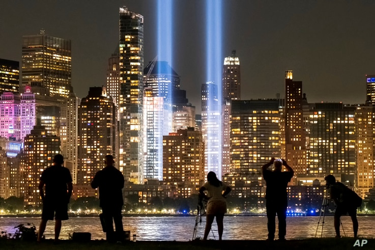 Spectators and photographers look across the Hudson River from Jersey City, N.J., at the Sept. 11 tribute lights in New York…