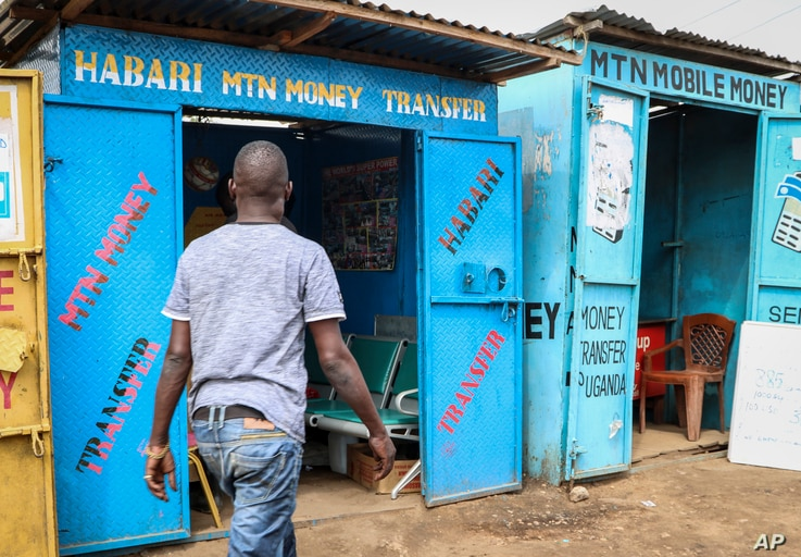 In this photo taken Tuesday, Sept. 10, 2019, a man walks past several mobile money kiosks in the capital Juba, South Sudan…