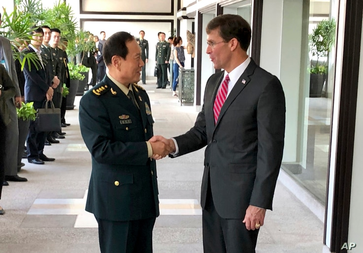 FILE - Chinese Defense Minister Wei Fenghe, left, greets U.S. Defense Secretary Mark Esper in Bangkok, Thailand, Nov. 18, 2019.