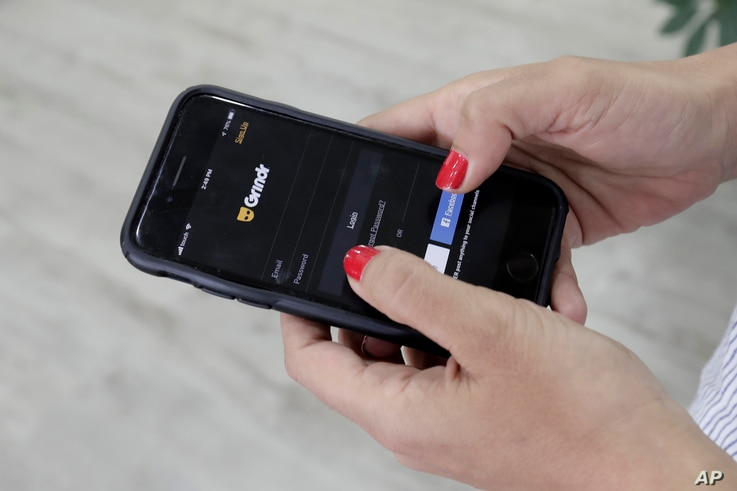 FILE - In this Wednesday, May 29, 2019 file photo, a woman checks the Grindr app on her mobile phone in Beirut, Lebanon. Dating…