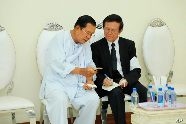 Cambodian Prime Minister Hun Sen, left, talks with dissolved main opposition Cambodia National Rescue Party leader Kem Sokha at…