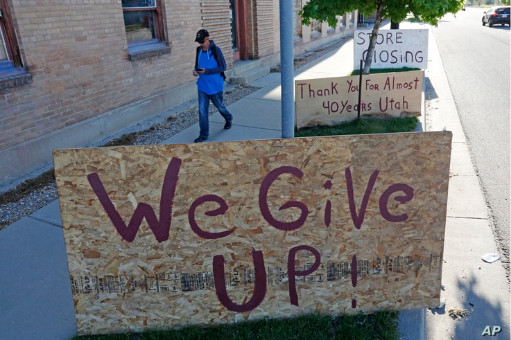 "A man walks past a ""we give up"" sign outside Euro Treasures Antiques Friday, May 8, 2020, in Salt Lake City. Scott Evans is…"