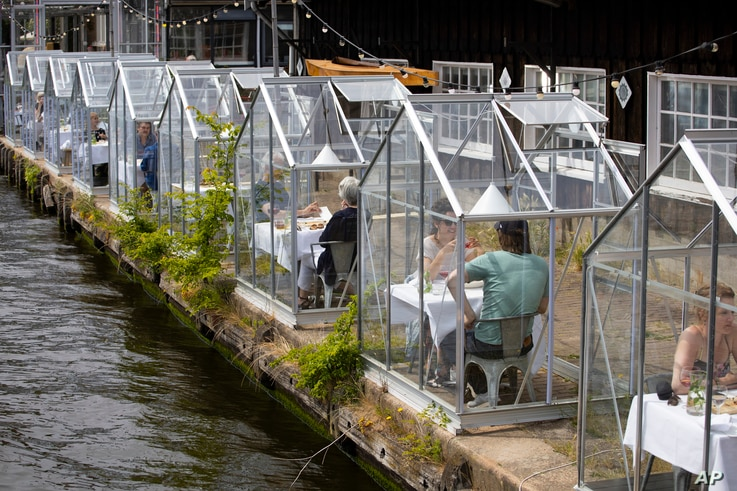 Customers seated in small glasshouses enjoy lunch at the Mediamatic restaurant in Amsterdam, Netherlands, Monday, June 1, 2020…
