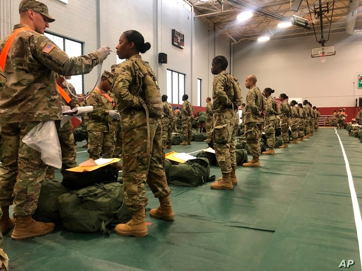 In this image provided by the U.S. Army, recent Army basic combat training graduates have their temperatures taken as they…