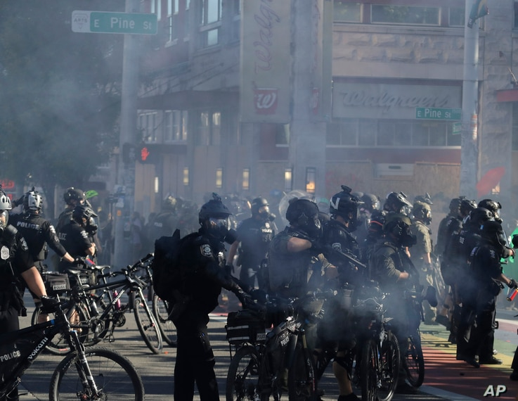 Seattle bicycle police officers wear gas masks and carry weapons as smoke rises and they clash with protesters, Saturday, July…