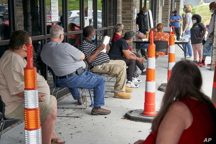FILE - In this  July 15, 2020, file photo, job seekers exercise social distancing as they wait to be called into the Heartland…