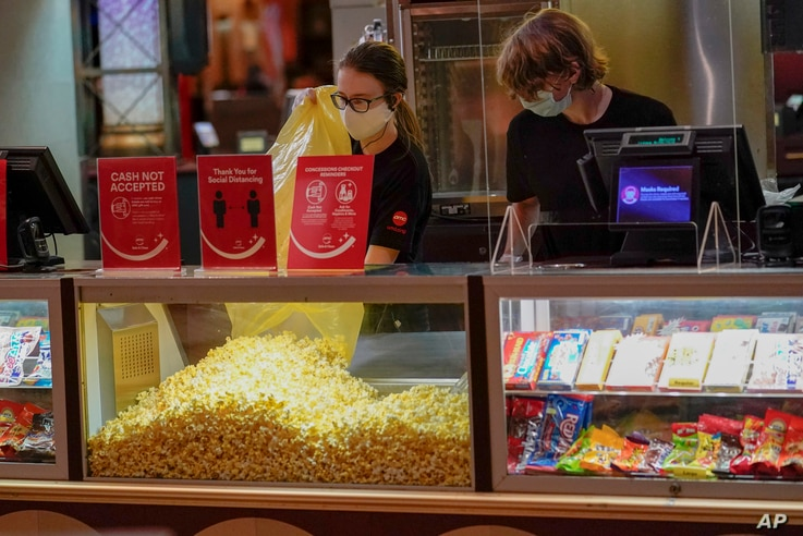Concessions workers stock the bins with popcorn and other treats as an AMC theater opens for some of the first showings since it shut down at the start of the COVID-19 pandemic, Aug. 20, 2020, in West Homestead, Pa.