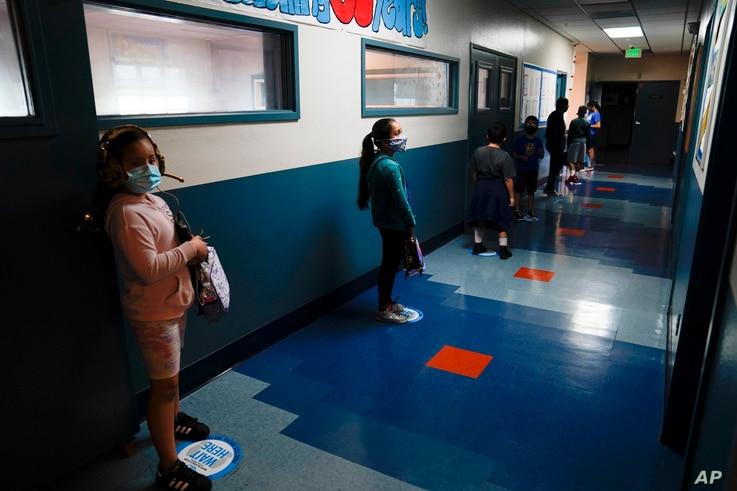 Los Angeles Unified School District students stand in a hallway socially distance during a lunch break at Boys & Girls Club of…