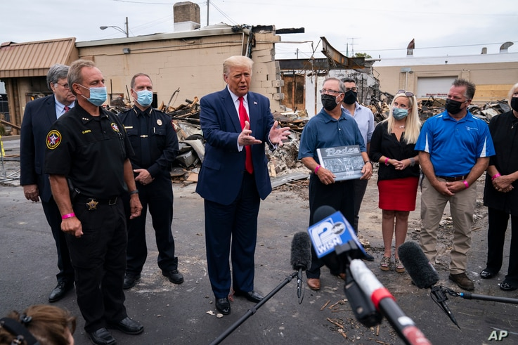 President Donald Trump tours an area on Tuesday, Sept. 1, 2020, damaged during demonstrations.