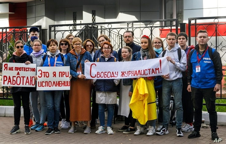 """Journalists of Belarusian TUT.BY media outlet hold banners reading """"I don't protest but work"""", """"This is me at work"""", """"Freedom for journalists!"""", from left to right, as they stand in front of police station in Minsk, Belarus, Sept. 2, 2020."""