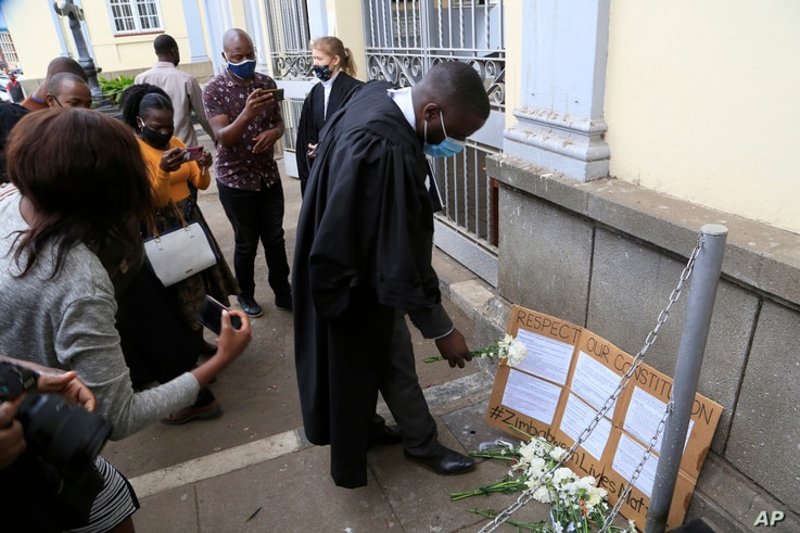 Lawyers stage a protest outside the High Court while awaiting a bail hearing for jailed journalist Hopwell Chin'ono, in Harare,…