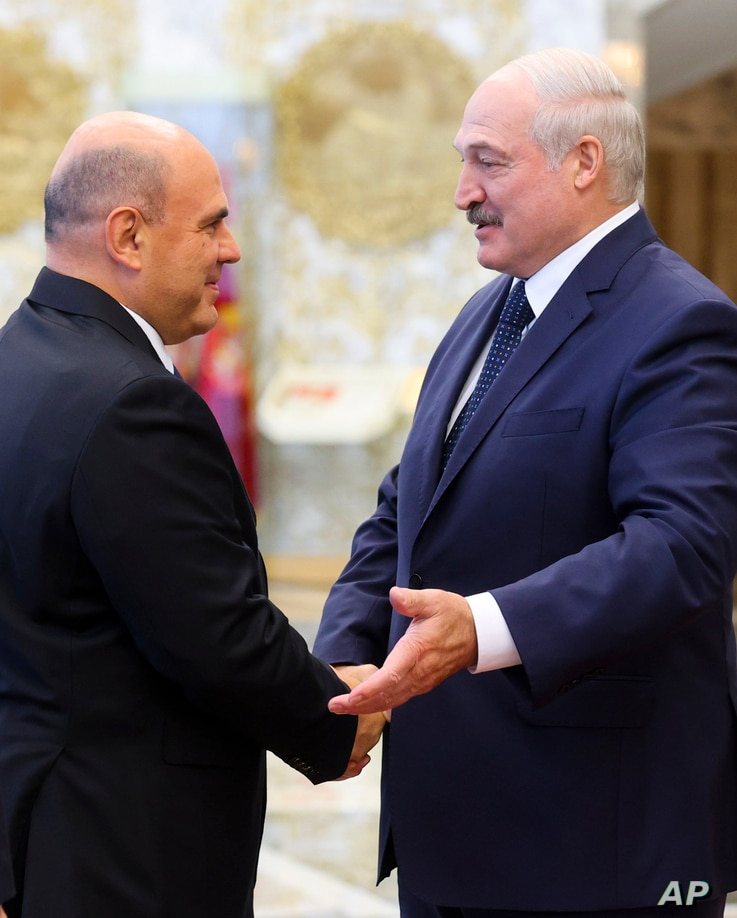 Russian Prime Minister Mikhail Mishustin, left, shakes hands with Belarusian President Alexander Lukashenko prior to their…