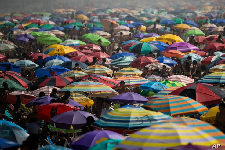 People enjoy the Ipanema beach amid the new coronavirus pandemic in Rio de Janeiro, Brazil, Sunday, Sept.6, 2020. Brazilians are packing the beaches and bars this weekend, taking advantage of a long holiday to indulge in normal life even as the COVID-19 pandemic rages on.