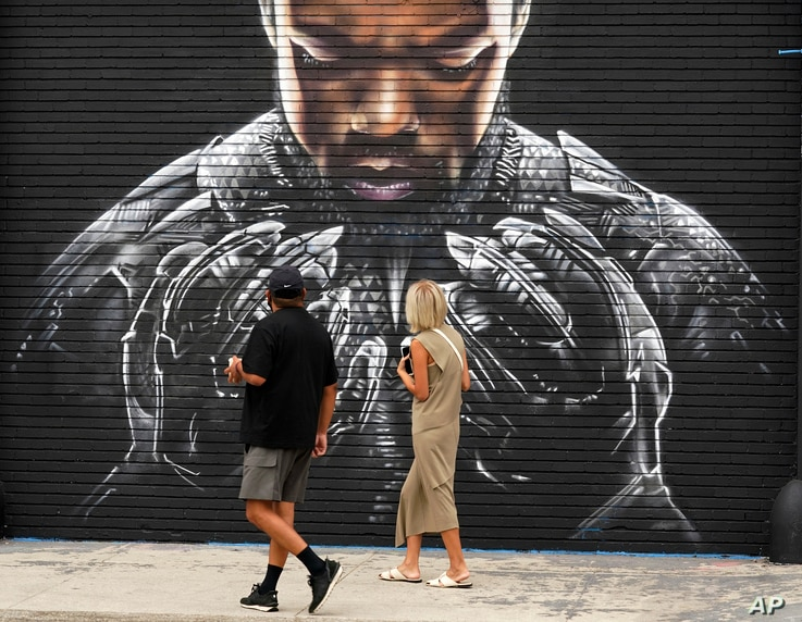 "Pedestrians look up at a mural by artist Shane Grammer of late actor Chadwick Boseman's character T'Challa from the 2018 film ""Black Panther,"", Sept. 8, 2020, in Los Angeles."