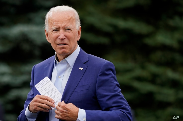 Democratic presidential candidate former Vice President Joe Biden places a note card in his jacket pocket as he speaks at a…