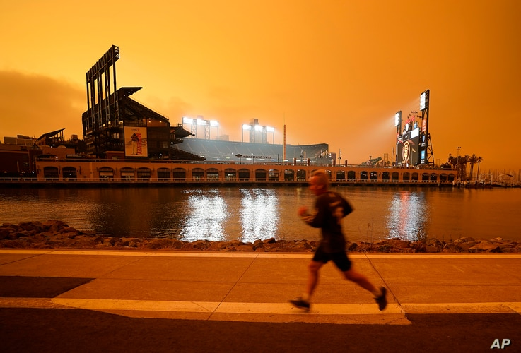 Under darkened skies from wildfire smoke, a jogger makes his way along McCovey Cove outside Oracle Park on Wednesday, Sept. 9,…