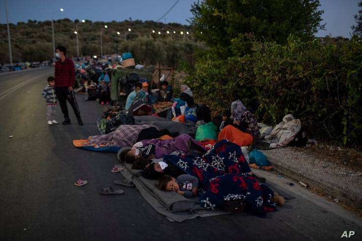 Migrants sleep on the road near the Moria refugee camp on the northeastern island of Lesbos, Greece, Thursday, Sept. 10, 2020…