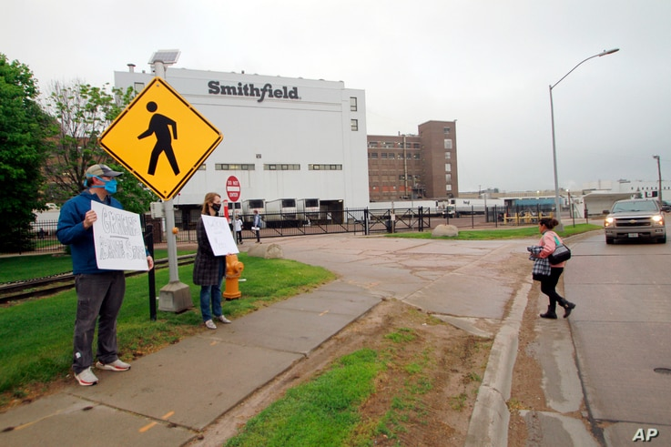 FILE - In this May 20, 2020, file photo, residents cheer and hold thank you signs to greet employees of a Smithfield pork…