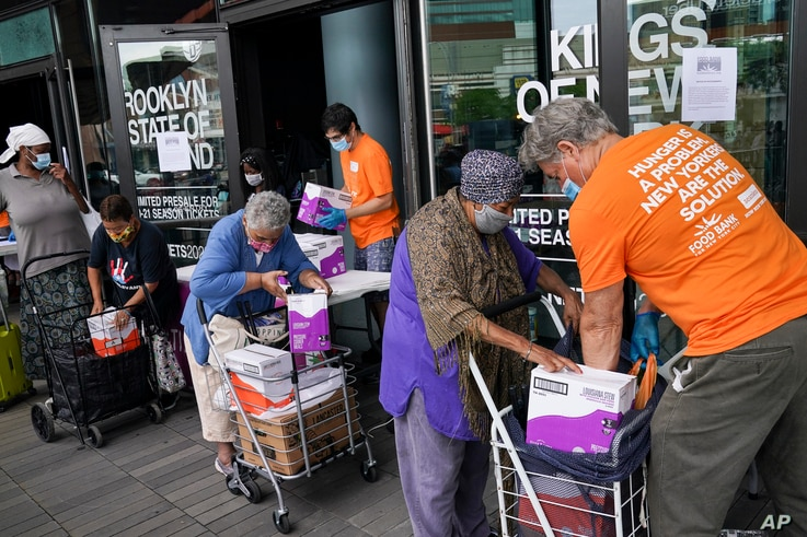 The elderly collect fresh produce and shelf-stable pantry items outside Barclays Center as Food Bank For New York City provides assistance to those in need due to the COVID-19 pandemic, Thursday, Sept. 10, 2020, in New York.