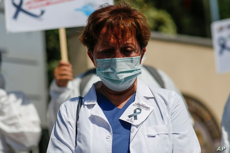 A health worker wearing a face mask to help prevent the spread of the coronavirus wears and a picture of a black ribbon to raise concerns over COVID-19 deaths and increasing numbers of patients, Istanbul, Sept. 15, 2020.