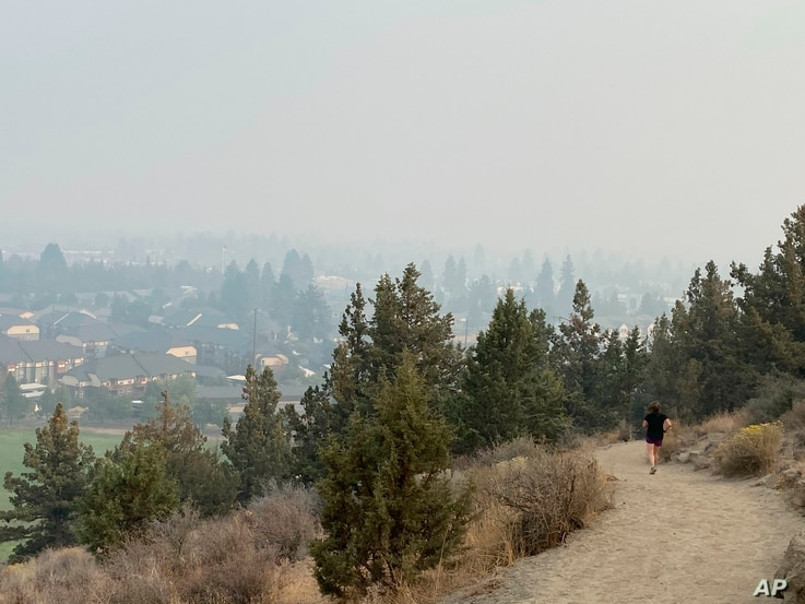 A runner descends a trail on Pilot Butte, a lava dome overlooking the city of Bend, Ore., Tuesday, Sept. 15, 2020. Wildfires…