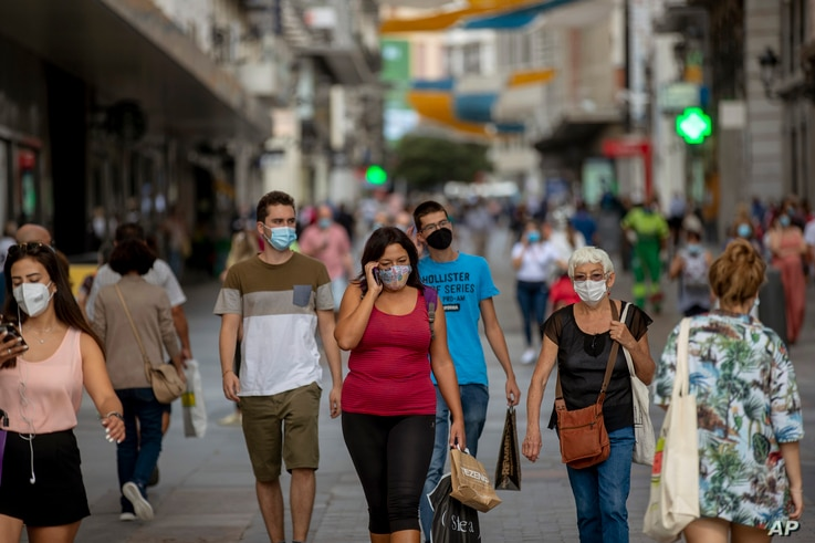 People wearing face masks to prevent the spread of coronavirus walk in downtown Madrid, Spain, Wednesday, Sept. 16, 2020. The…