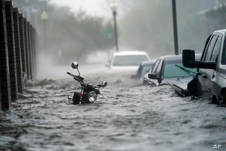 Floodwaters move on the street, Wednesday, Sept. 16, 2020, in Pensacola, Fla. Hurricane Sally made landfall Wednesday near Gulf…