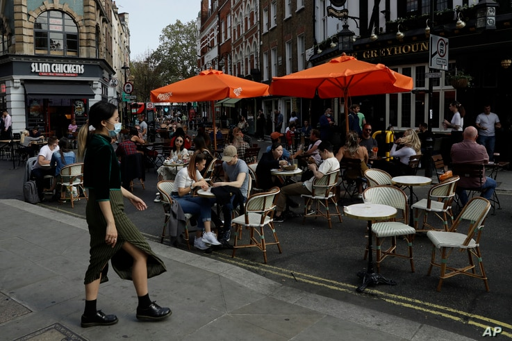 People sit outside on a street closed to traffic to try to reduce the spread of coronavirus so bars, cafes and restaurants can…