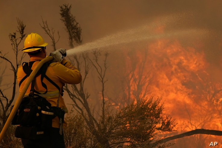 Jesse Vasquez, of the San Bernardino County Fire Department, hoses down hot spots from the Bobcat Fire on Saturday, Sept. 19,…