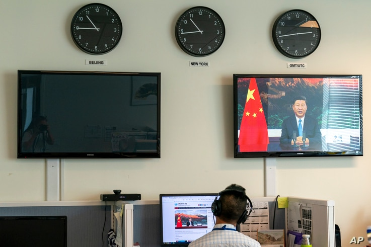 A reporter with the Xinhua Press Agency watches as President Xi Jinping is seen on a video screen remotely addressing the 75th…