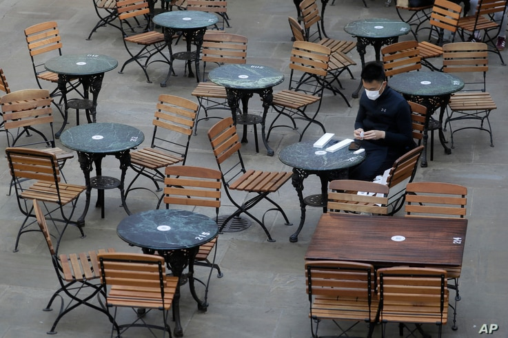 A man sits in an empty cafe in London, Thursday, Sept. 24, 2020, after Britain's Prime Minister Boris Johnson announced a range…