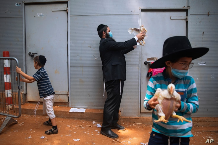 An ultra-Orthodox Jewish man wearing a face mask during a nationwide three-week lockdown to curb the spread of the coronavirus, swings a chicken over his head as part of the Kaparot ritual, in Bnei Brak, Israel, Sept 24, 2020.