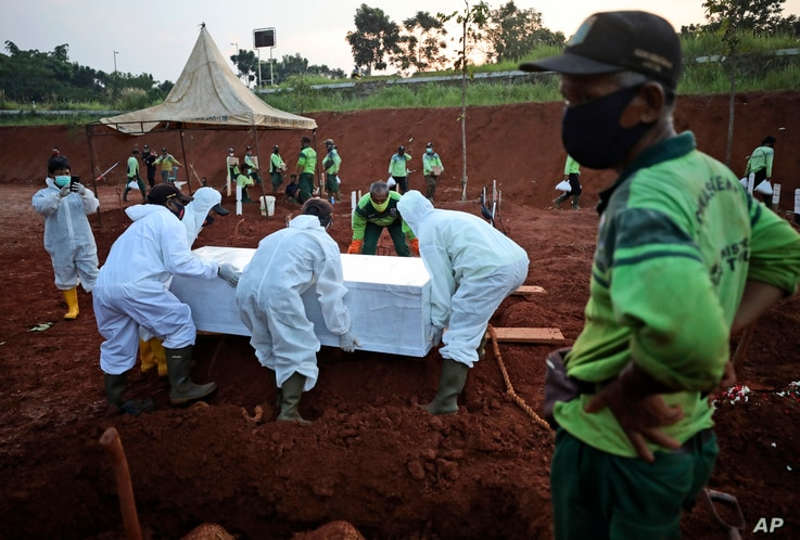 Workers lower a coffin containing the body of a suspected COVID-19 victim into a grave during a burial at the special section…