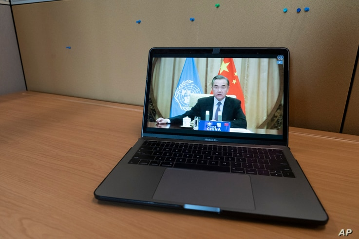 Chinese Foreign Minister Wang Yi is seen on a computer monitor at United Nations headquarters as he speaks during a virtual…