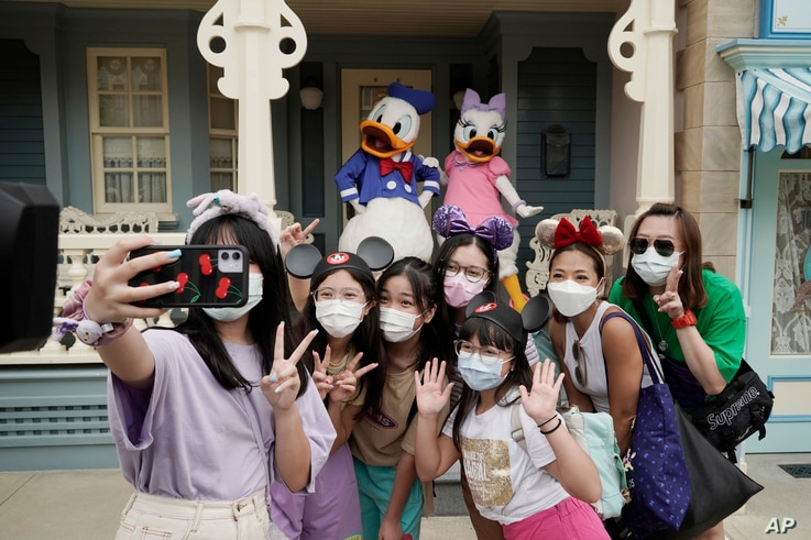 Visitors wearing face masks take a selfie with the iconic cartoon characters Donald Duck and Daisy Duck at the Hong Kong…