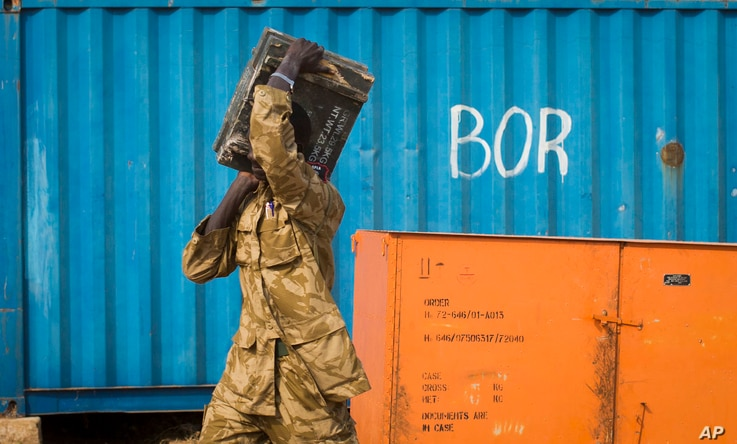A South Sudanese government soldier carries an ammunition box from storage at the airport in Bor, Jonglei State, South Sudan…
