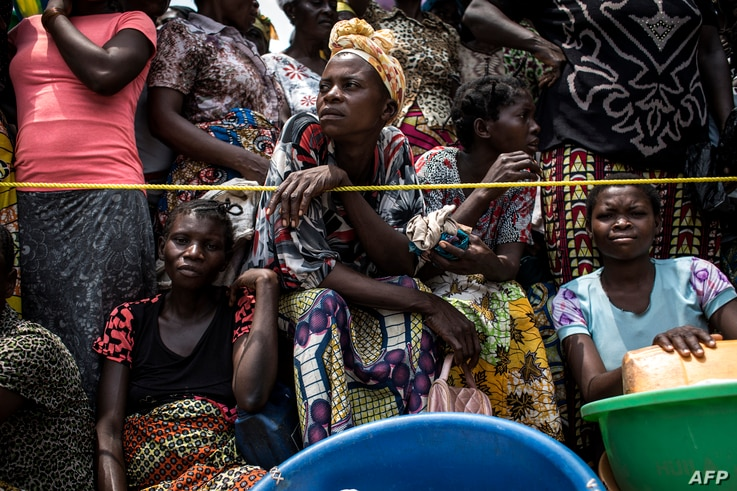 FILE - A woman looks on while people wait for their ration of food to be handed out at a food distribution Oct. 25, 2017 in Kasala, in the restive province of Kasai, Democratic Republic of Congo.