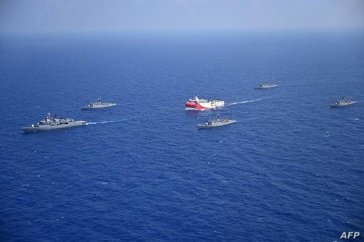 FILE - A handout photograph released by the Turkish Defense Ministry Aug. 12, 2020, shows Turkish seismic research vessel Oruc Reis (C) as it is escorted by Turkish Naval ships in the Mediterranean Sea, off Antalya, Aug. 10, 2020.