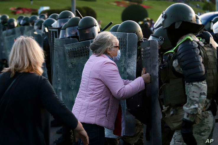 A woman argues with riot police during an opposition rally to protest the presidential inauguration of Alexander Lukashenko, in Minsk, Belarus, Sept. 23, 2020.