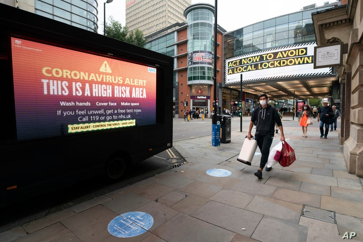 "Public information messages in central Manchester England, are posted after British Prime Minister Boris Johnson set out new restrictions to last ""perhaps six months"" to slow the renewed spread of coronavirus."