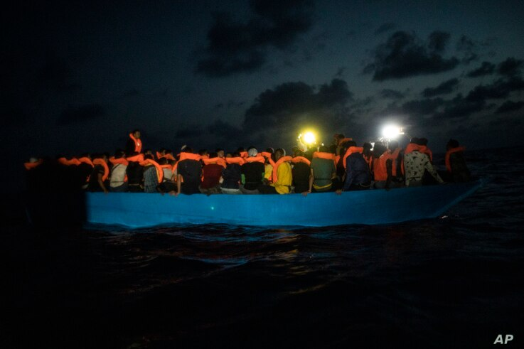 Dozens of African migrants wait to be assisted by a team of aid workers of the Spanish NGO Open Arms, after spending more than 20 hours at sea, in the Central Mediterranean sea, Sept. 8, 2020.