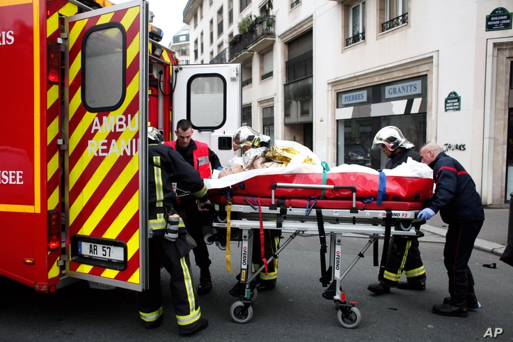 FILE - An injured person is transported to an ambulance after a shooting, at the French satirical newspaper Charlie Hebdo's office, in Paris, Jan. 7, 2015.